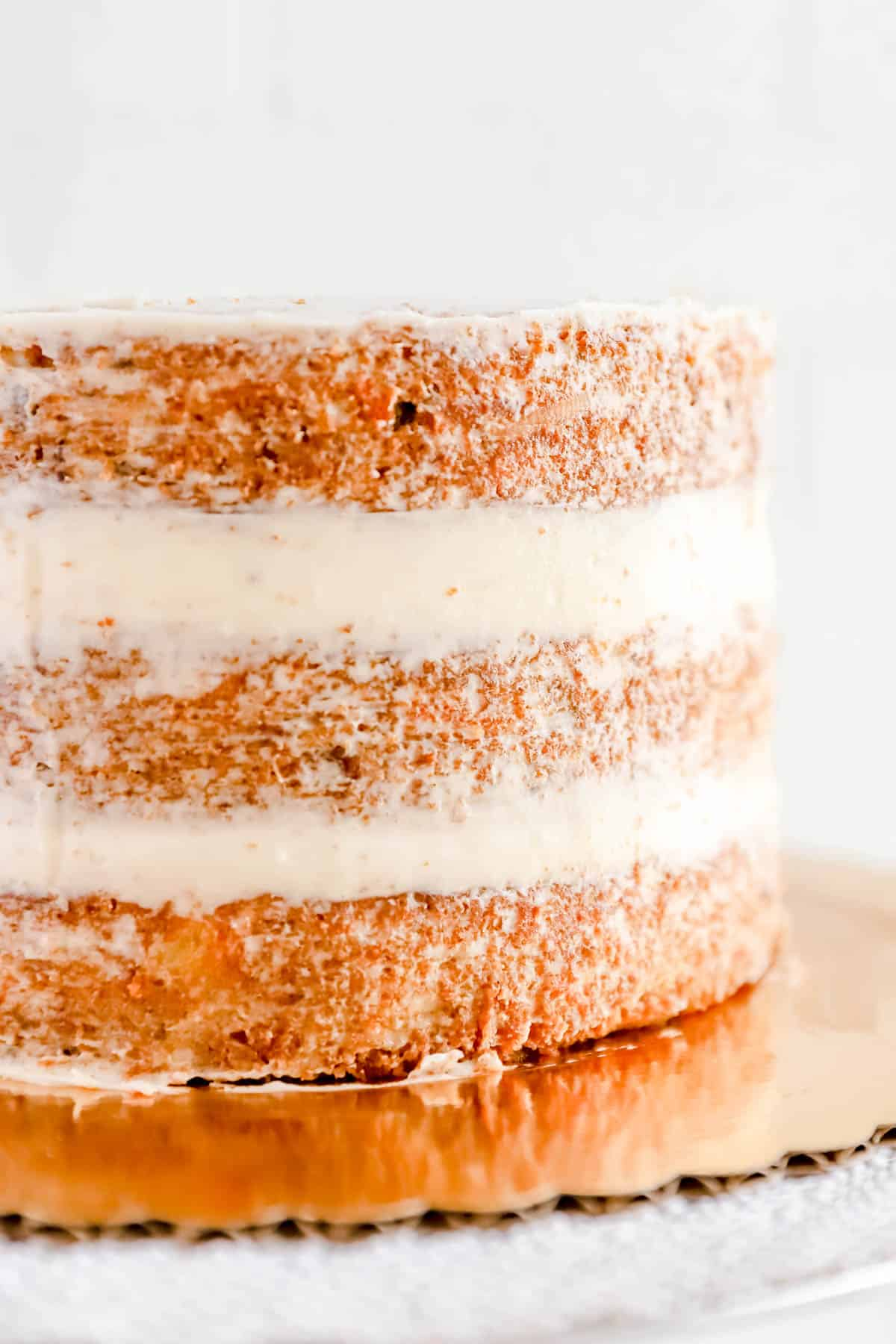 3 baked round carrot cake layers filled and crumb coated with cream cheese frosting.