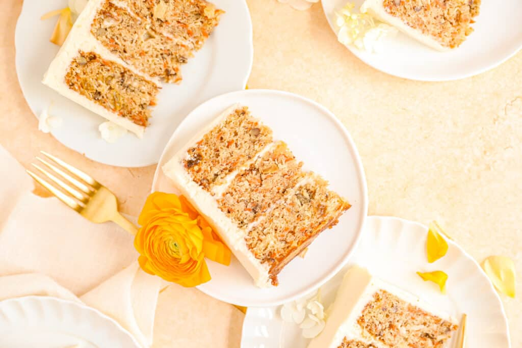 old-fashioned carrot cake slices on plates stacked up with ranunculus flowers for decoration.