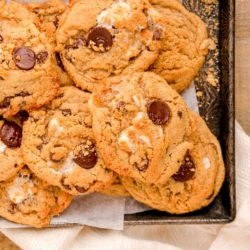baked s'mores cookies piled on an antique baking sheet.