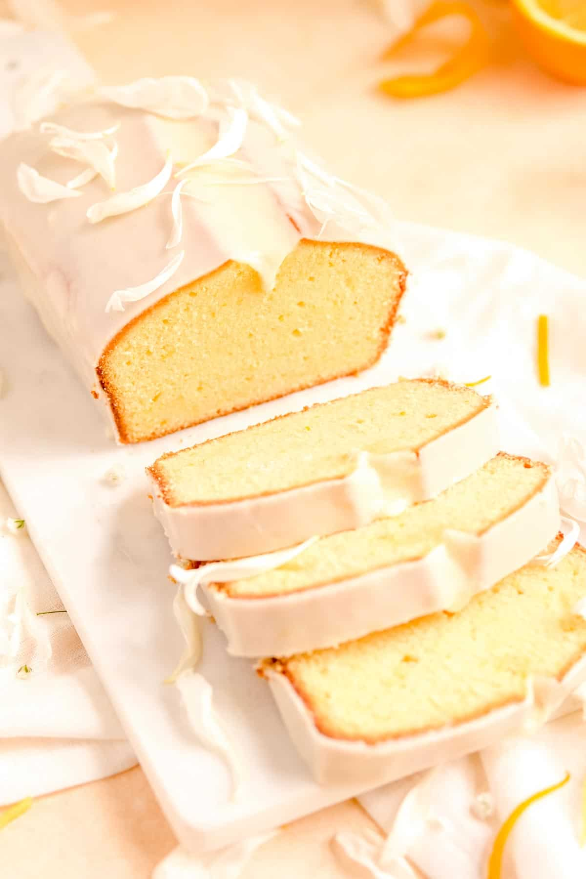 a partially sliced, glazed citrus cream cheese pound cake from a 45 degree angle and oranges in the background.