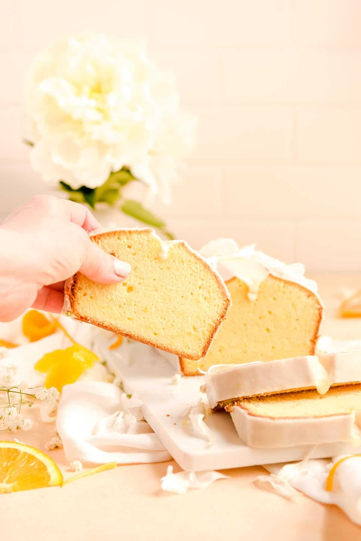 someone grabbing a slice of glazed citrus pound cake from a a table with flowers and orange slices on it.