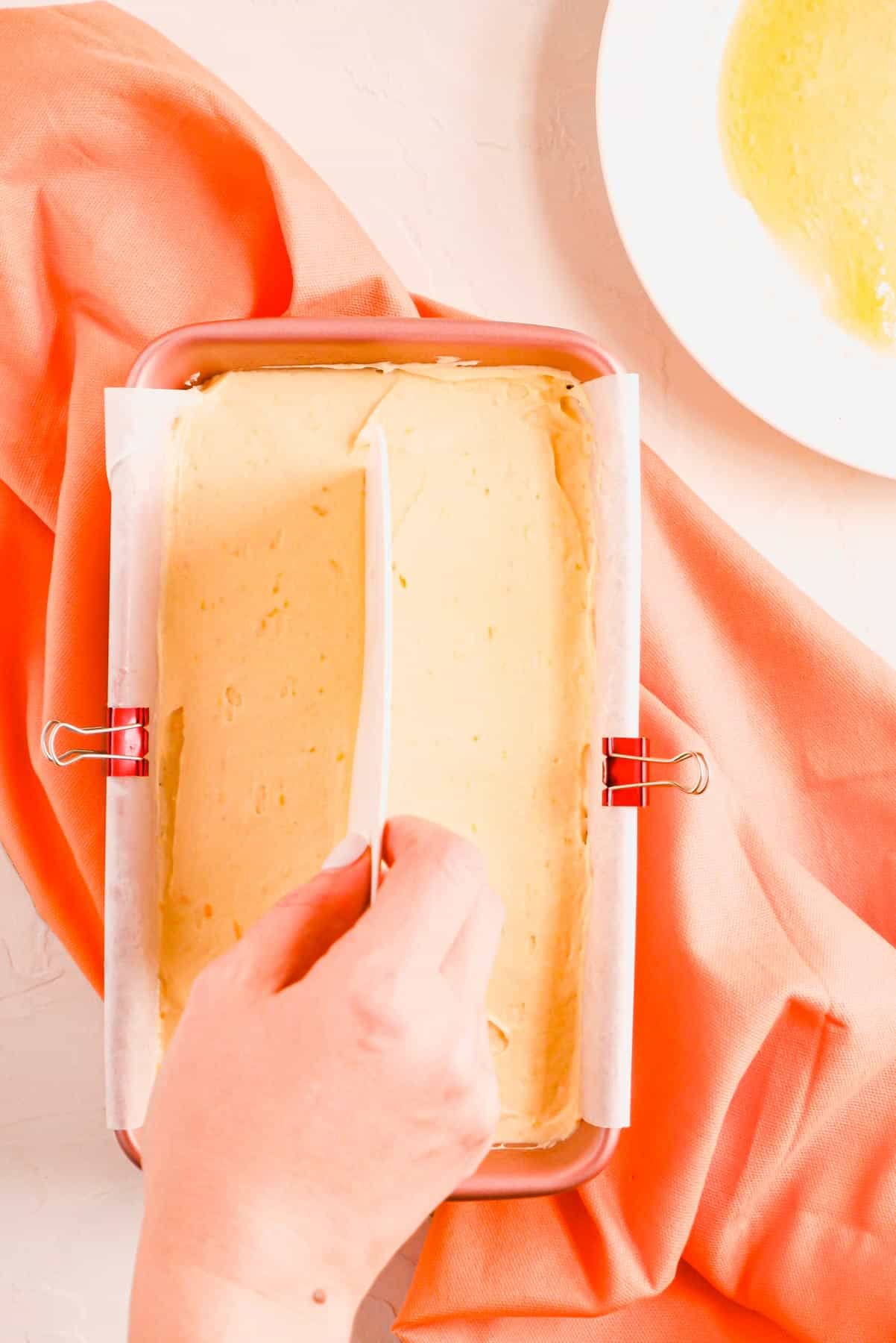 a hand using a bench knife to make a butter line in the middle of the pan of pound cake batter