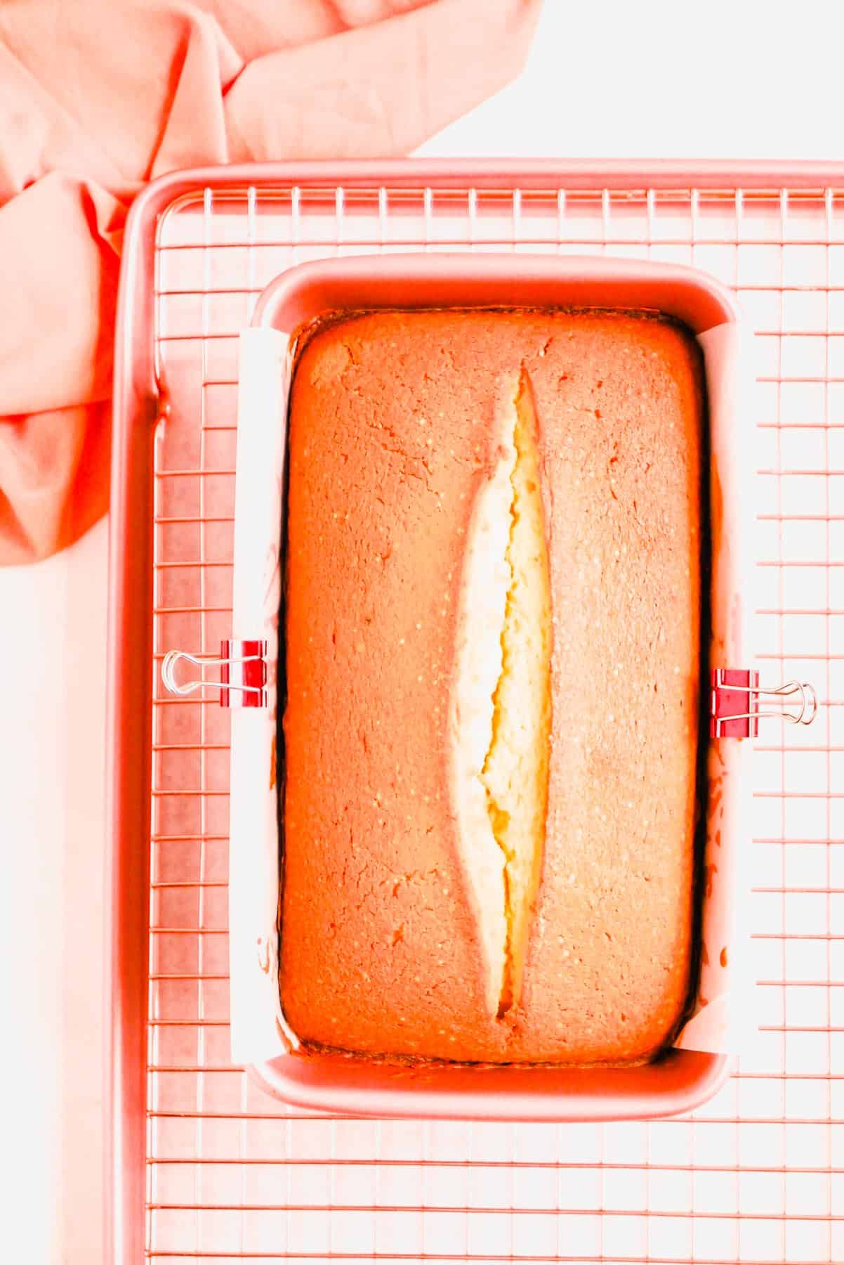 a fully baked citrus pound cake in a pink pan on a copper wire rack.