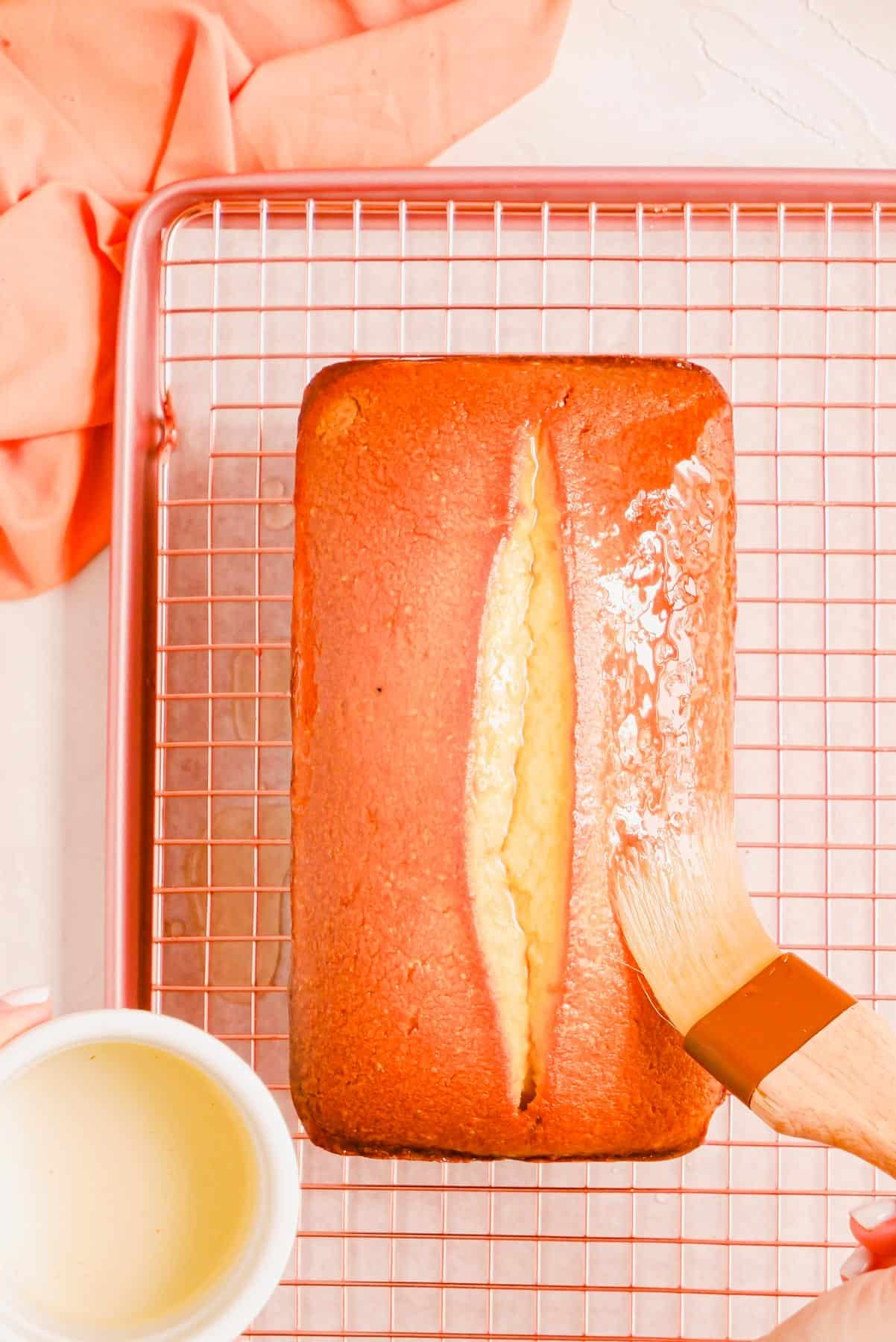 a hand actively glazing a baked pound cake with lemon glaze form a bowl in the corner