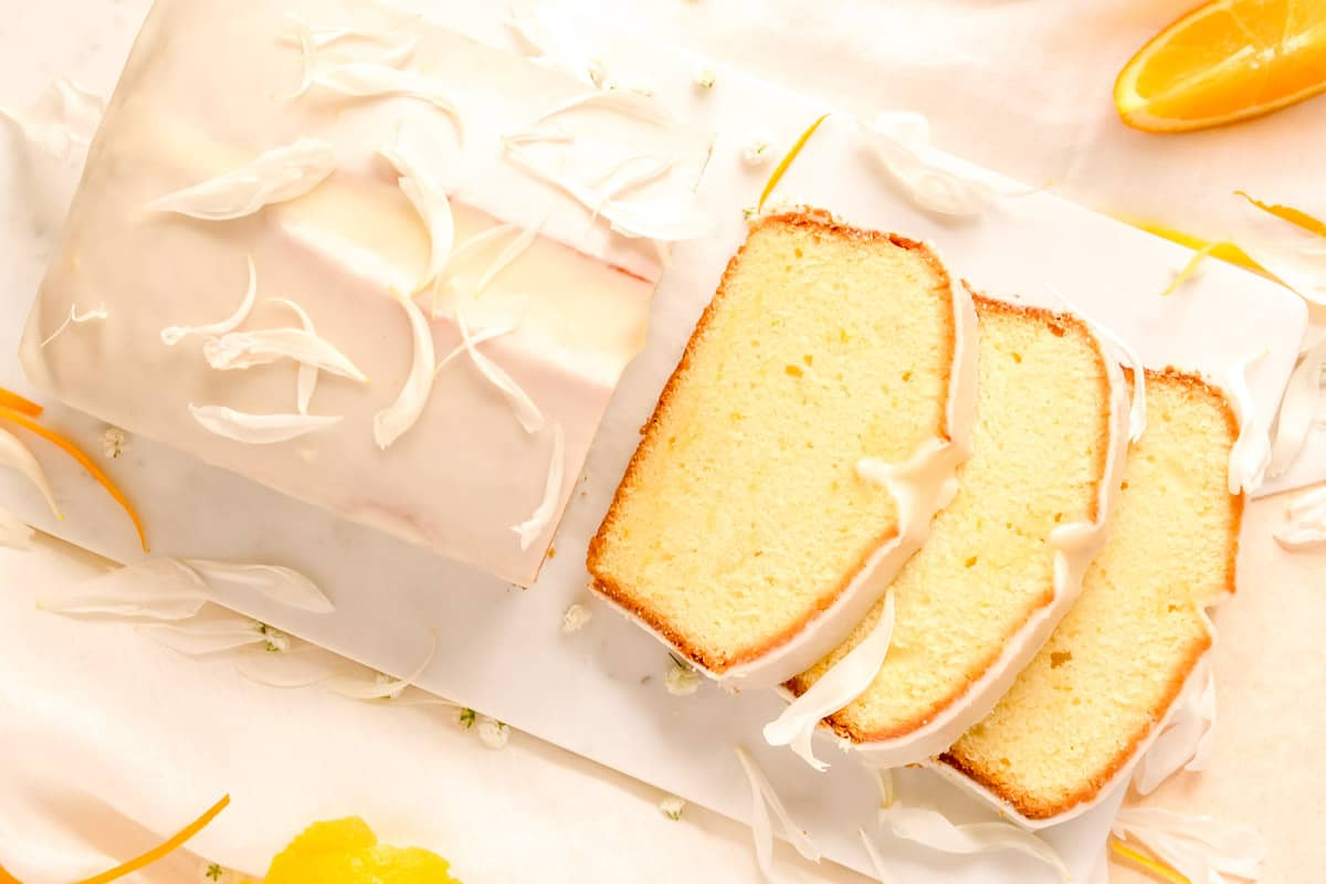 a partially sliced citrus cream cheese pound cake from above on a marble board with orange and lemon slices on the table.