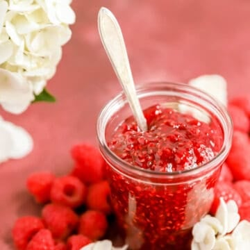 a clear glass jar of homemade raspberry jam surrounded by raspberries and flowers.