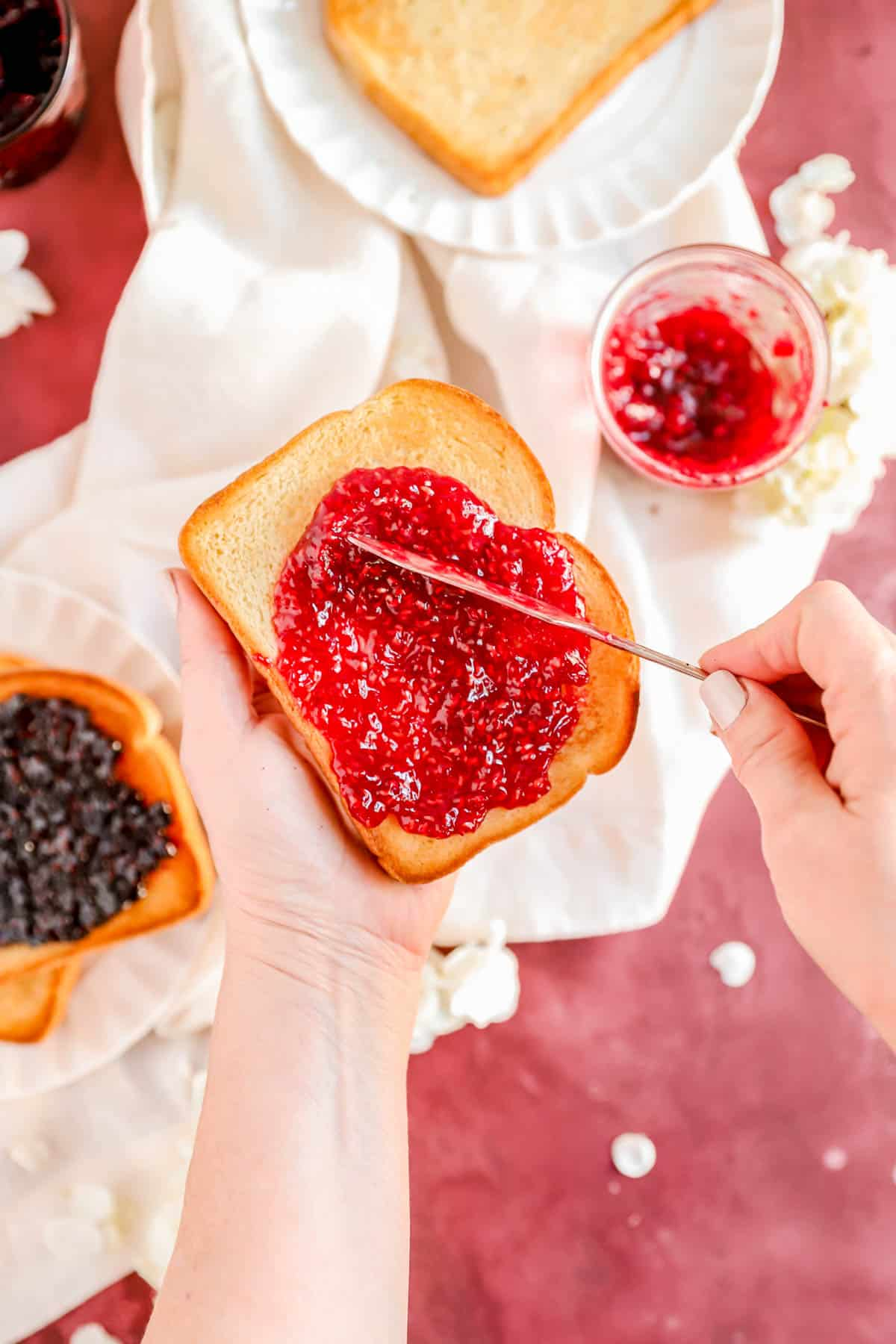 a hand holding a piece of toast and spreading homemade red raspberry jam on it.