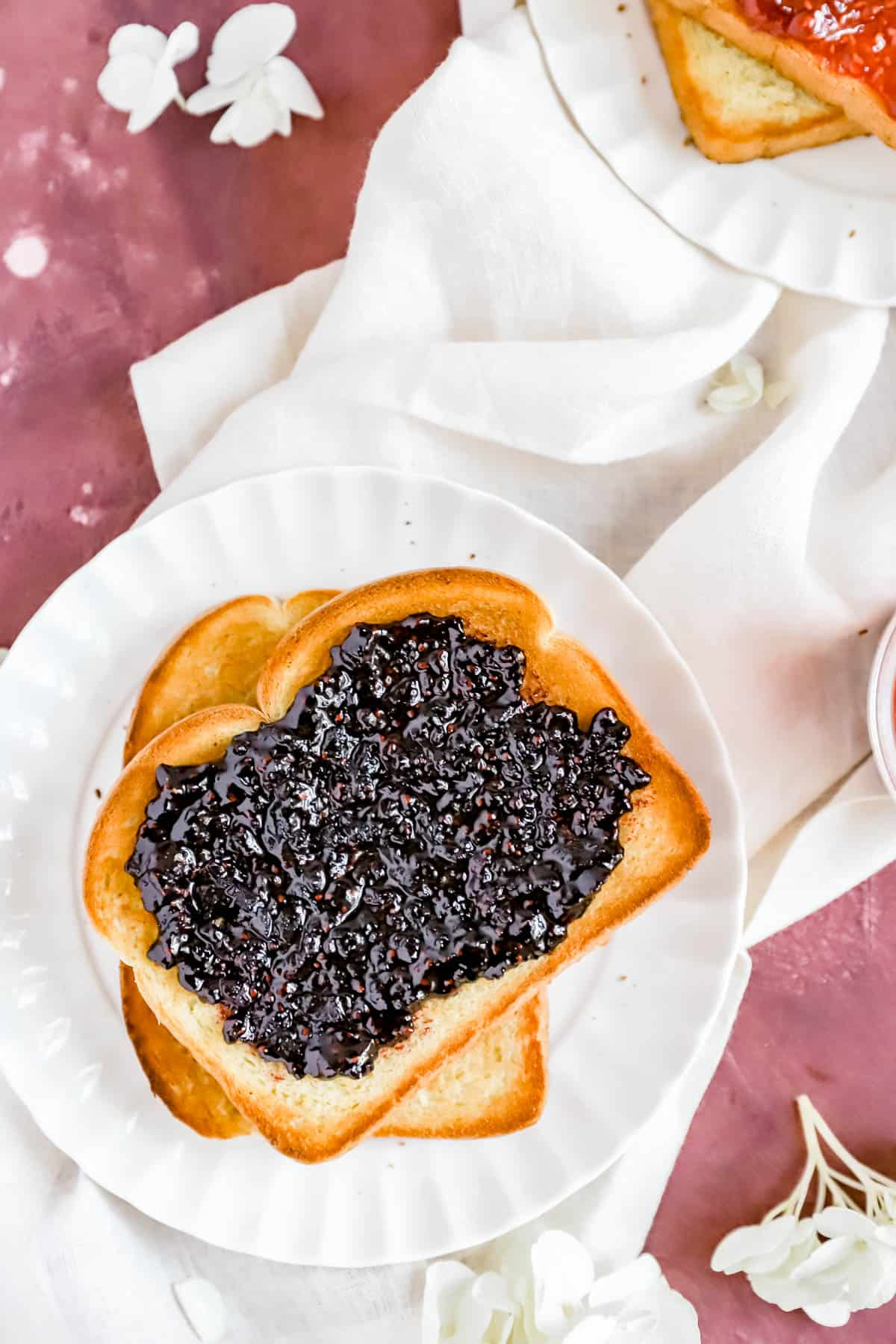 a slice of toast with homemade black raspberry jam on it and another piece of toast below.