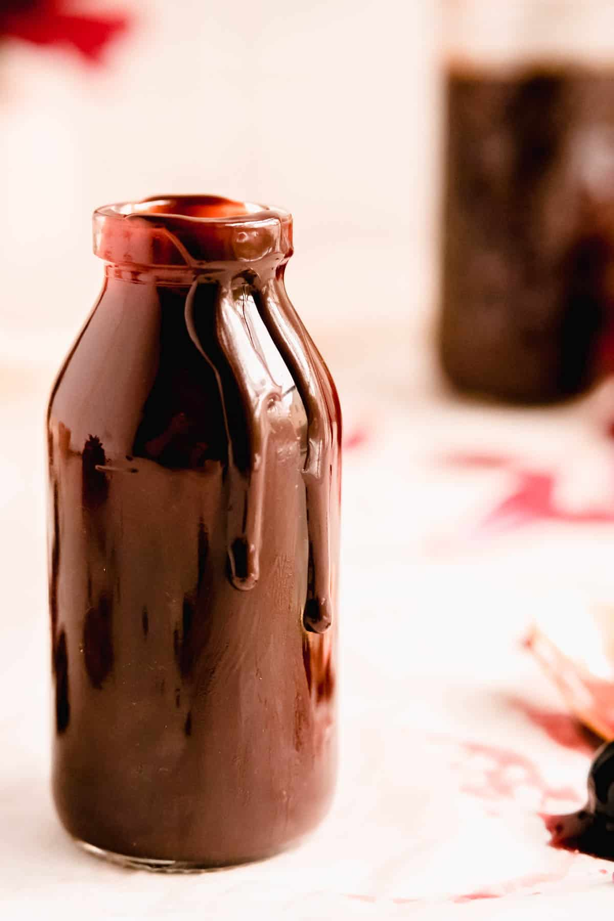 a jar with two big drops of hot fudge sauce dripping down the side with another jar of fudge in the background.