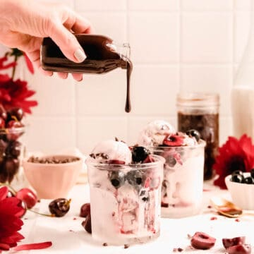 homemade hot fudge mid-pour from a bottle onto a cherry ice cream sundae.