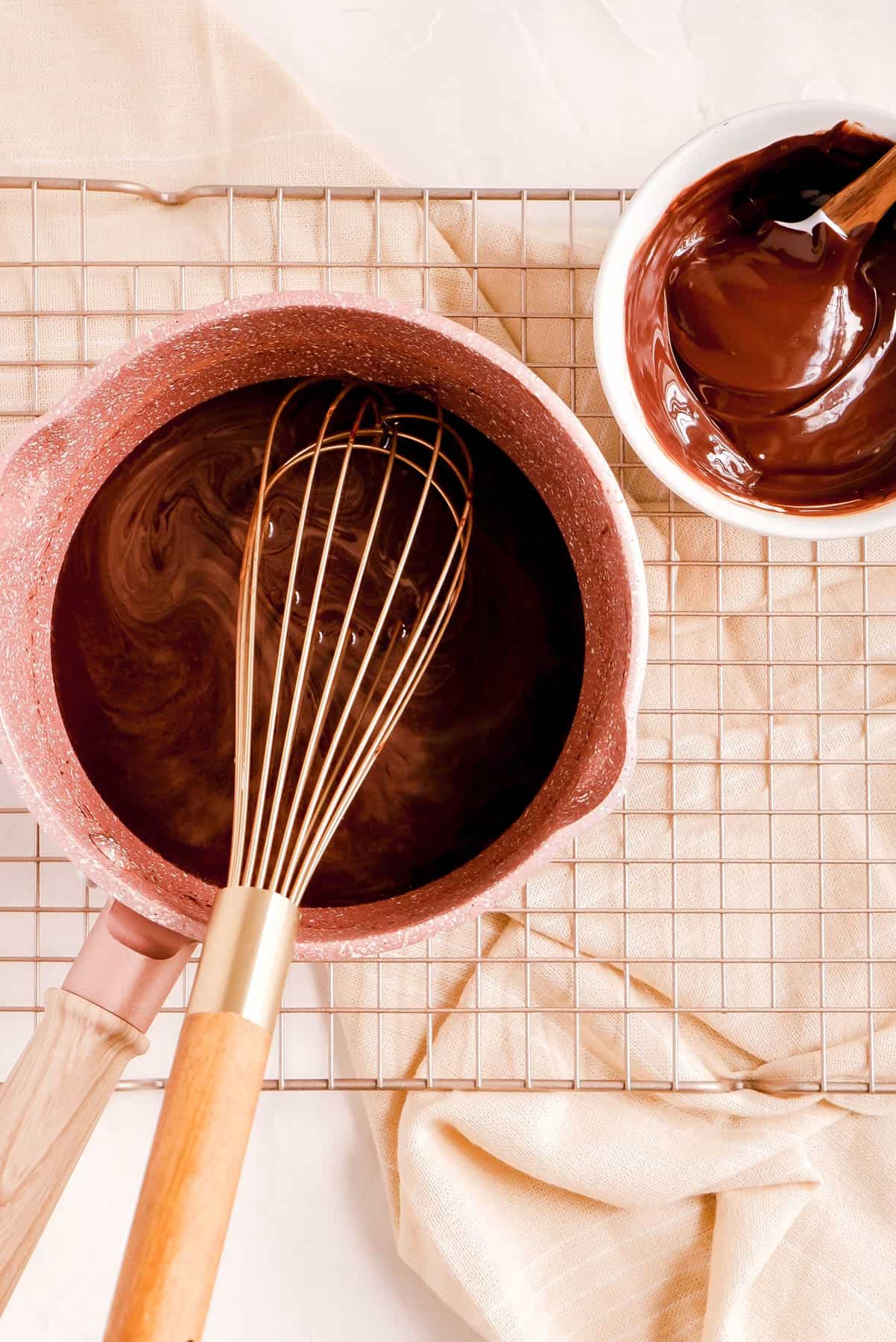 hot fudge sauce ingredients in a pot with a gold whisk on a copper wire rack with a bowl of melted chocolate on the side.