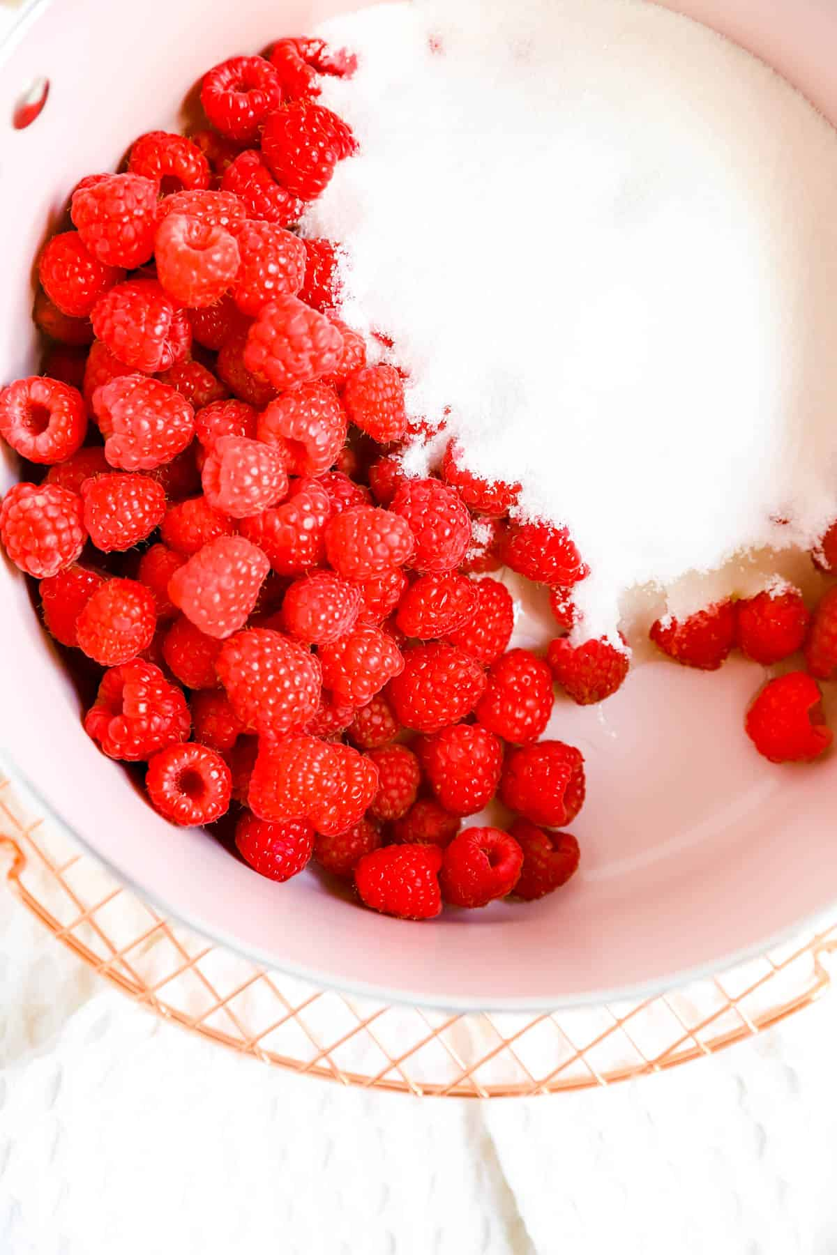 a pink pot on a cooling rack with raspberries, sugar, and lemon juice in it.