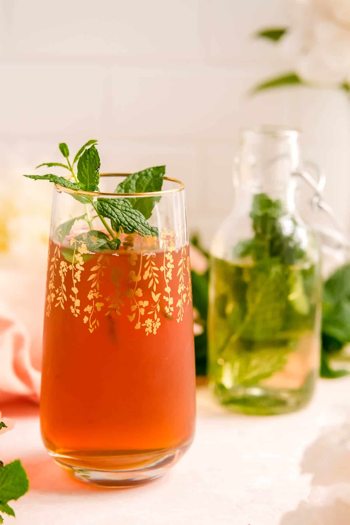a glass of iced tea with a partial bottle of mint syrup in the background.