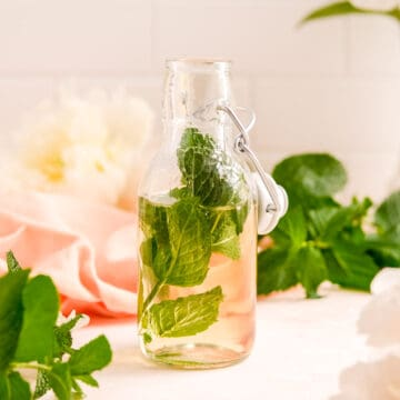 a partial bottle of mint simple syrup with a mint leaf in it.