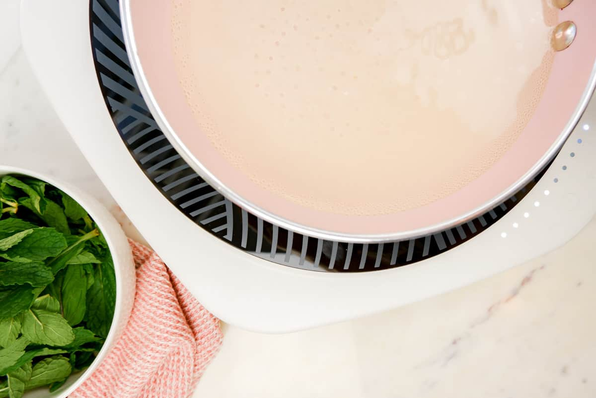 a pink pan on an induction stove with water and sugar in it starting to bubble with mint leaves in a bowl on the side.