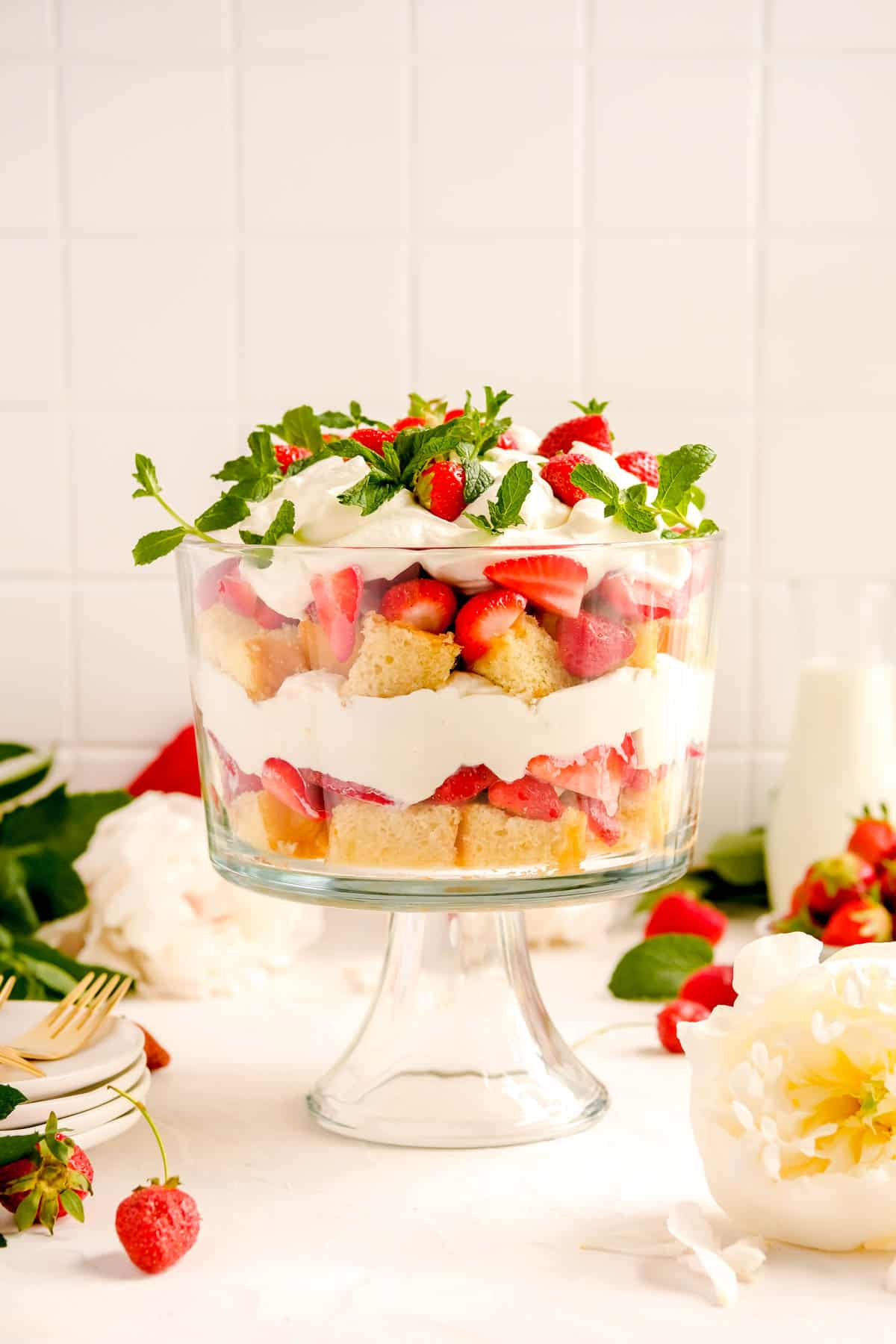 a strawberry trifle from the side showing the layers with plates, forks and flowers on a table.