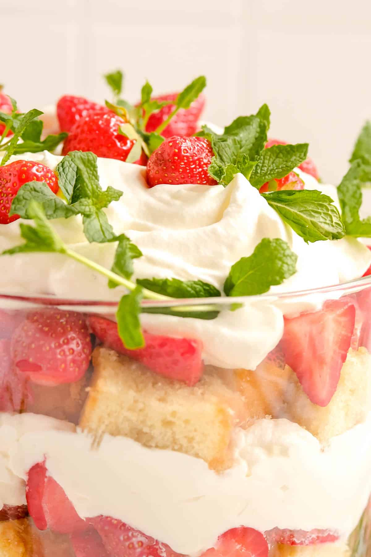 close-up of strawberry trifle in a trifle dish from the side with fresh mint leaf garnish.