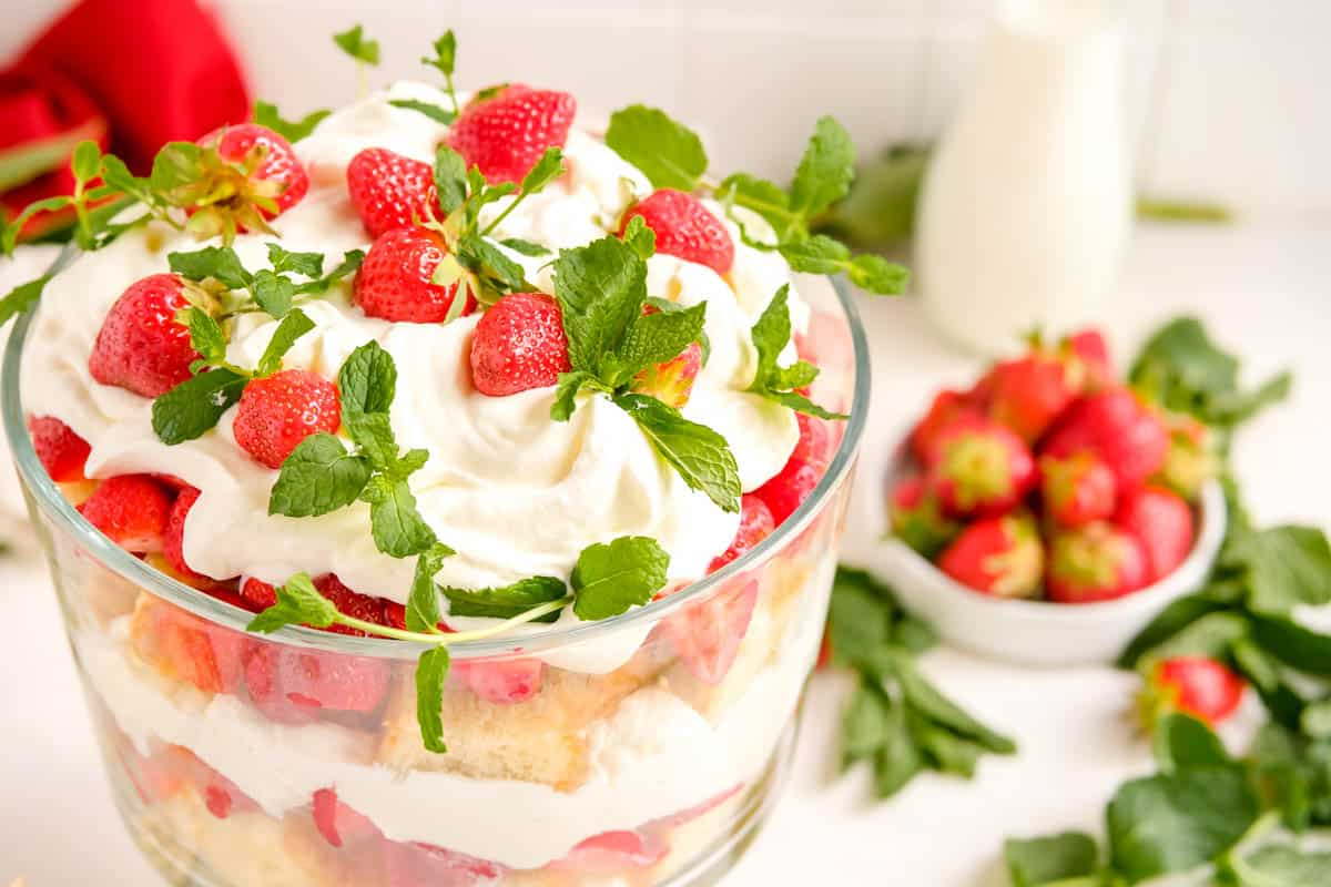 a filled strawberry trifle dish from the side garnished with berries and fresh mint, with a bowl of berries in the background.