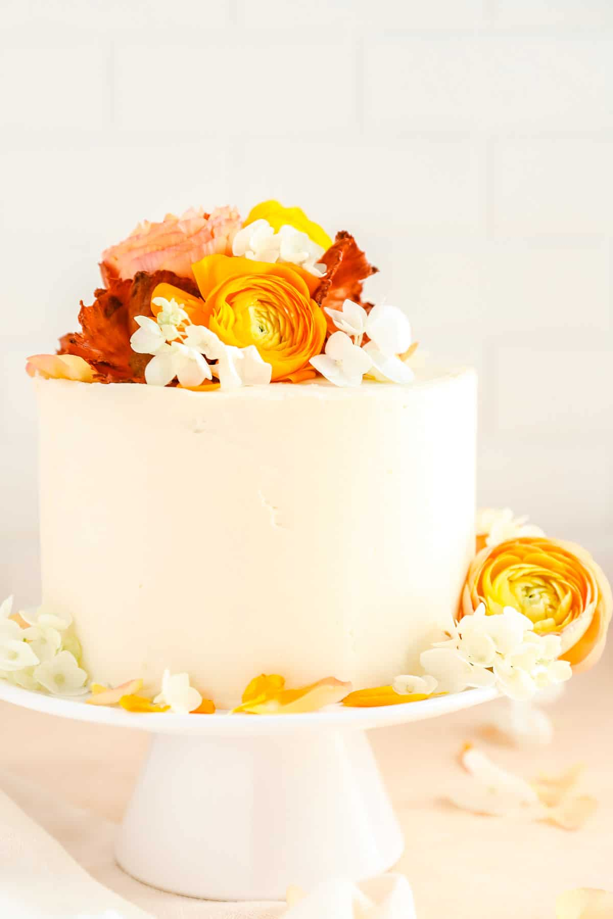 a cake covered in smooth white frosting with hydrangea and ranunculus flowers on top.