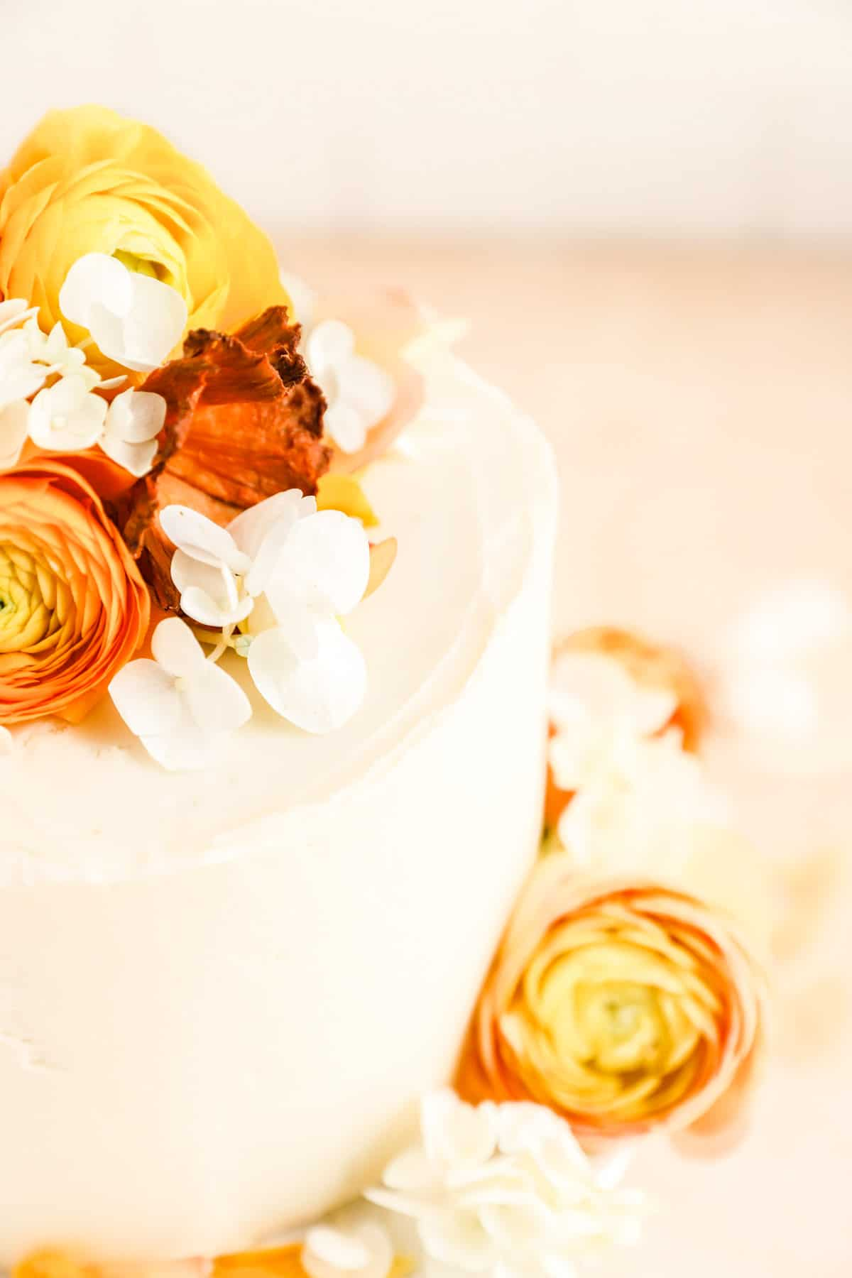 a close up of a cream cheese frosted carrot cake decorated with flowers.
