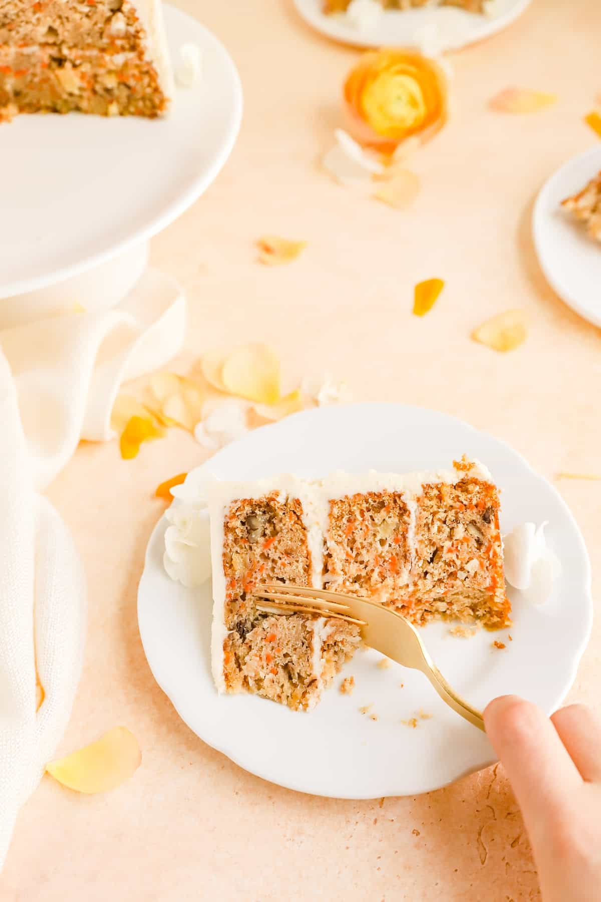 a hand using a fork to take a bite out of a piece of carrot cake.