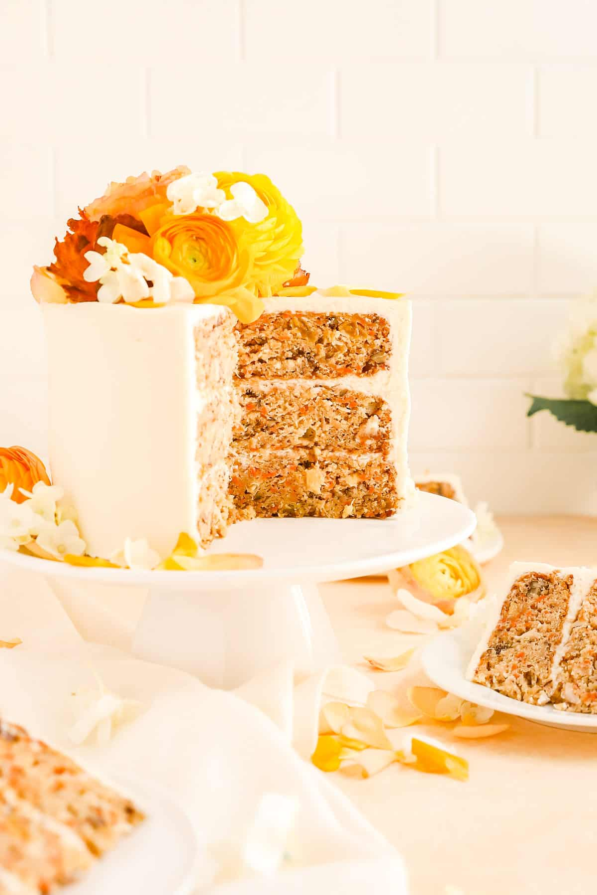 a carrot cake on a cake plate with a few slices cut our and on plates.