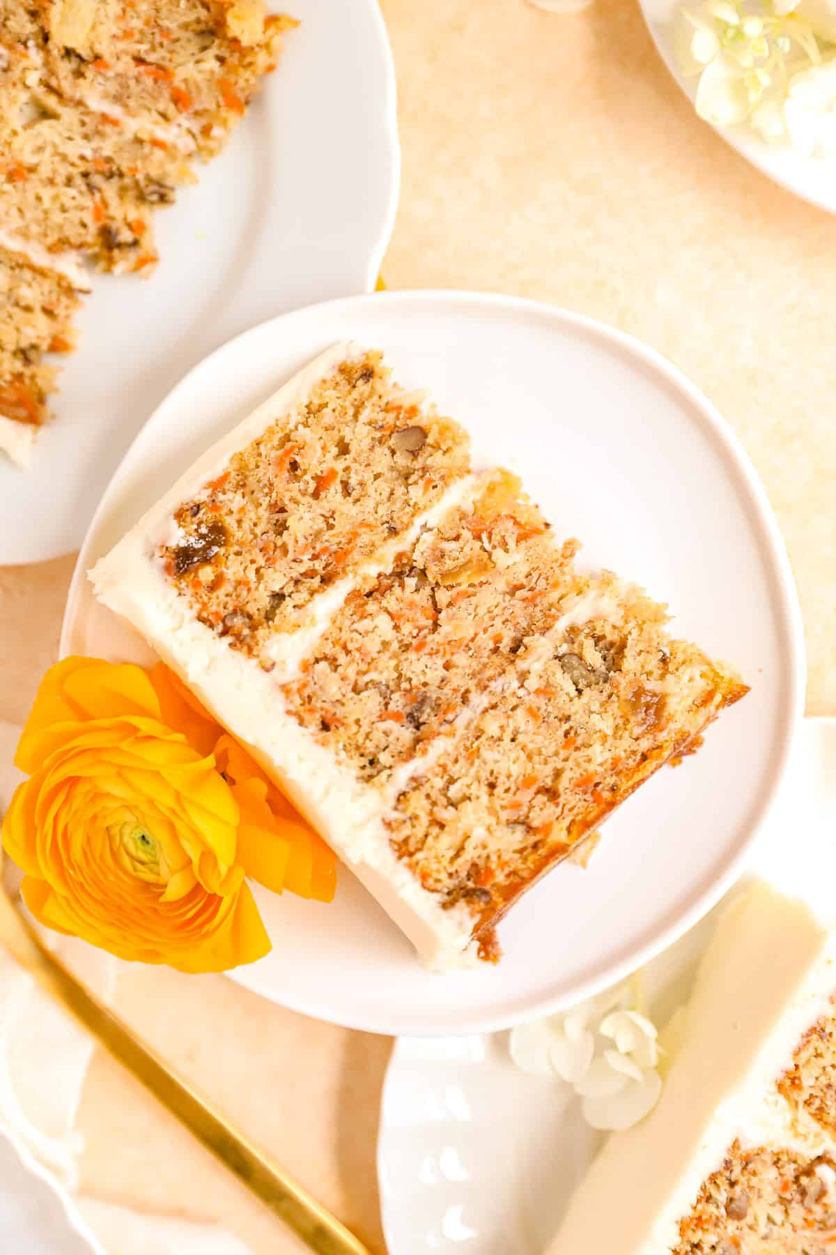 carrot cake with pineapple slices on plates stacked up with ranunculus flowers for decoration.