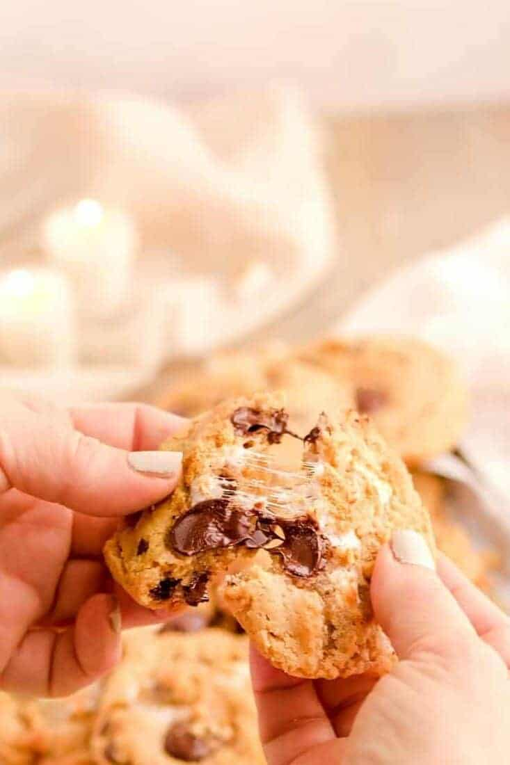 two hands breaking a hot and chewy smores cookie in half with strings of chocolate and marshmallow between the halves.