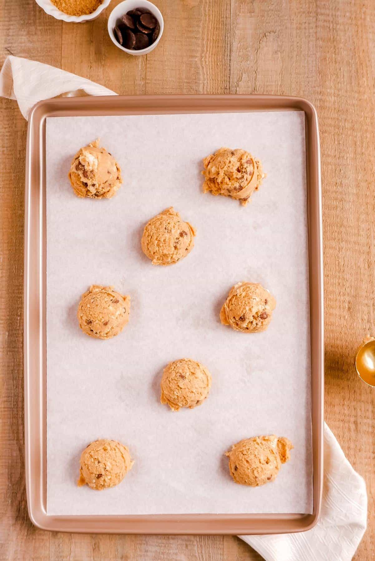 scooped smores cookie dough balls on a parchment-lined gold baking sheet.