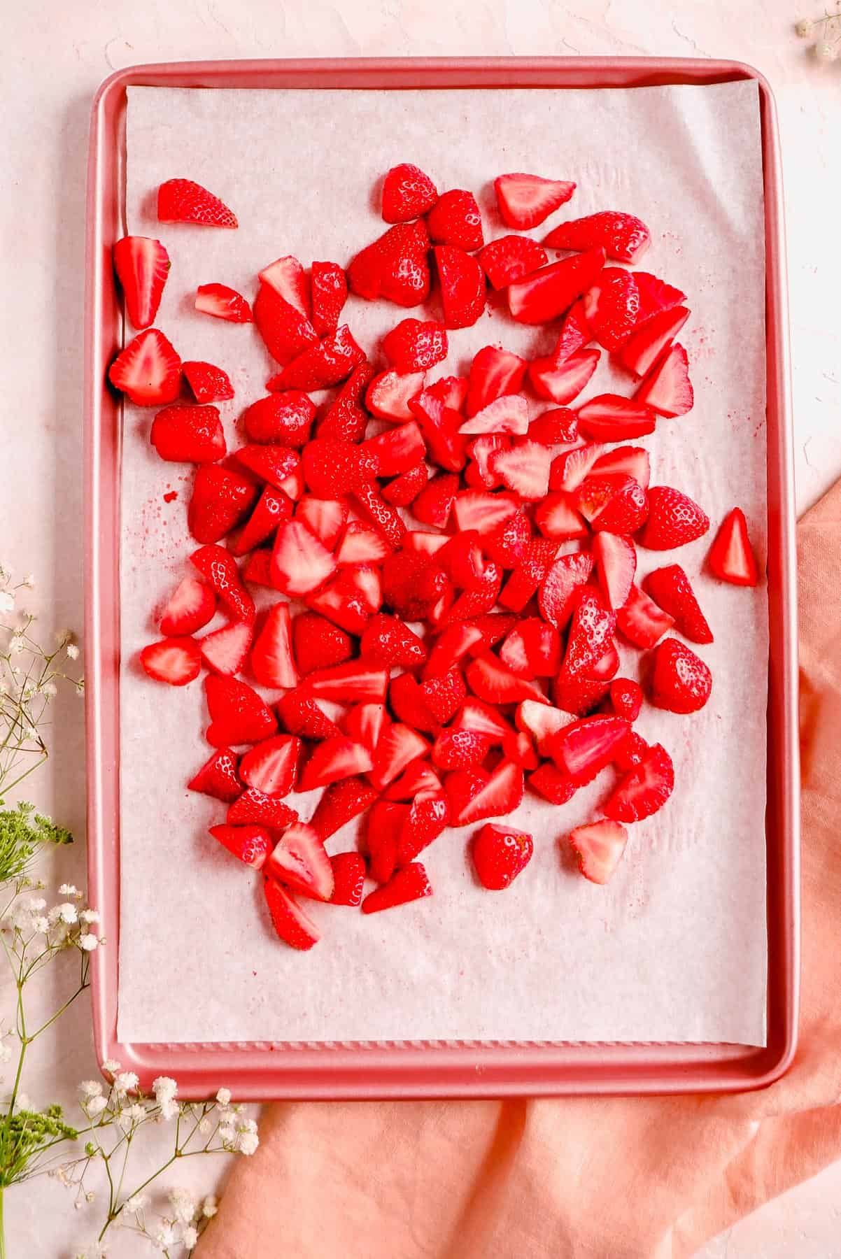 quartered fresh strawberries in a parchment lined pink baking pan.