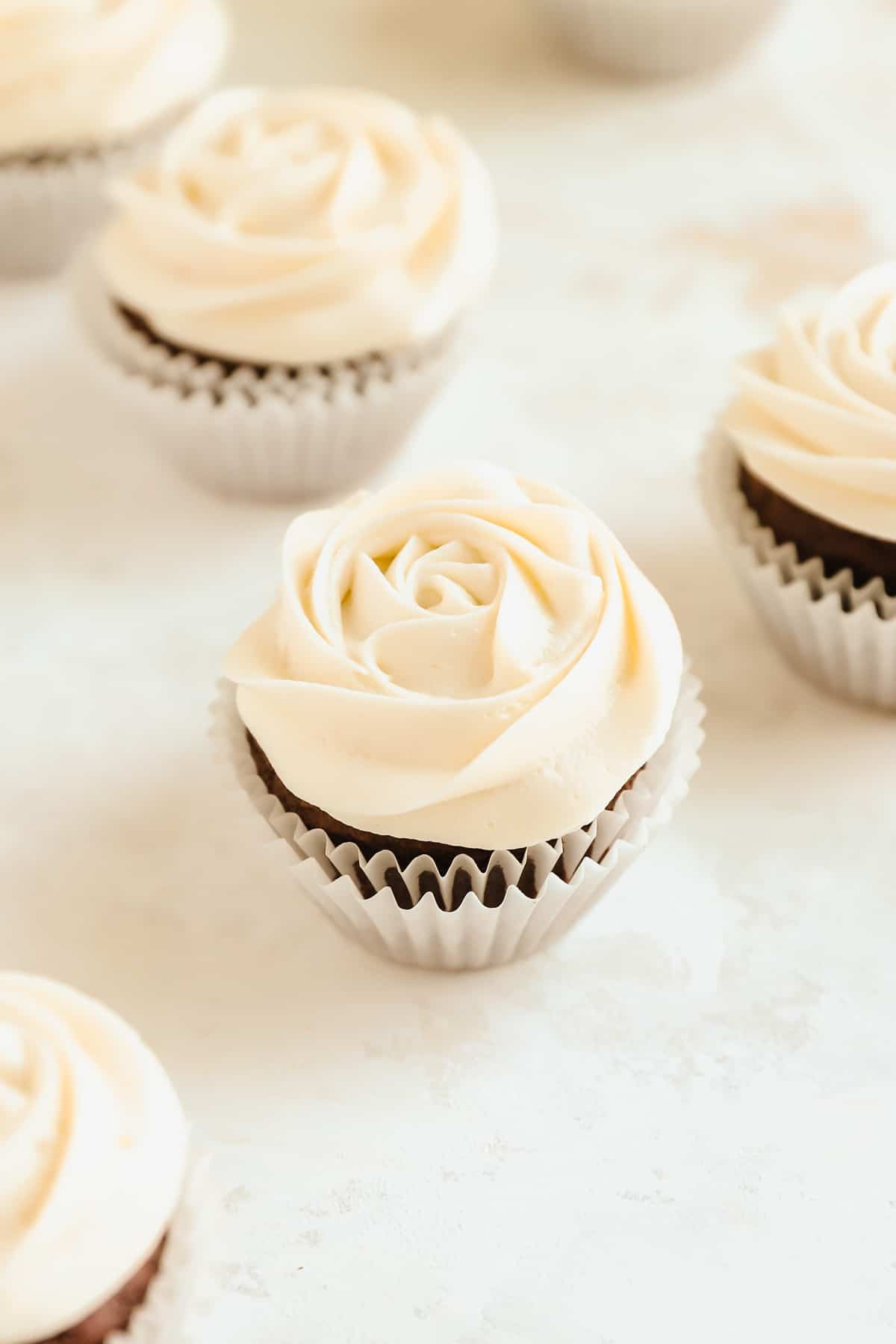 a close up of chocolate cupcakes with rosettes of cream cheese frosting on top.