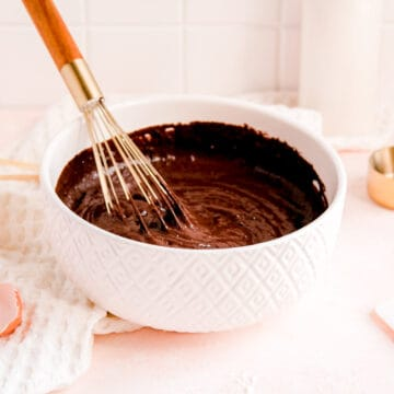 a white bowl of chocolate cake batter with a gold and wood whisk in it