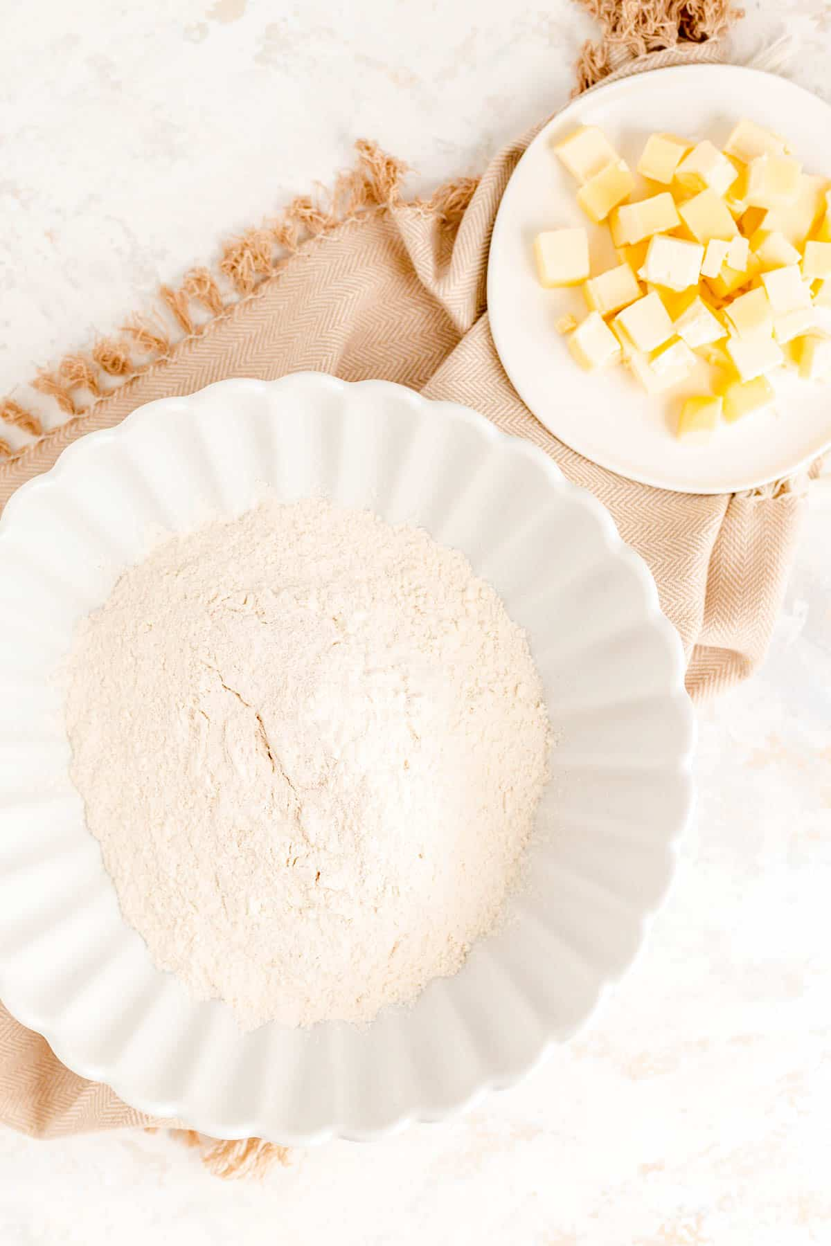 a bowl of dry ingredients and a small plate of cold butter cubes on a brown towel