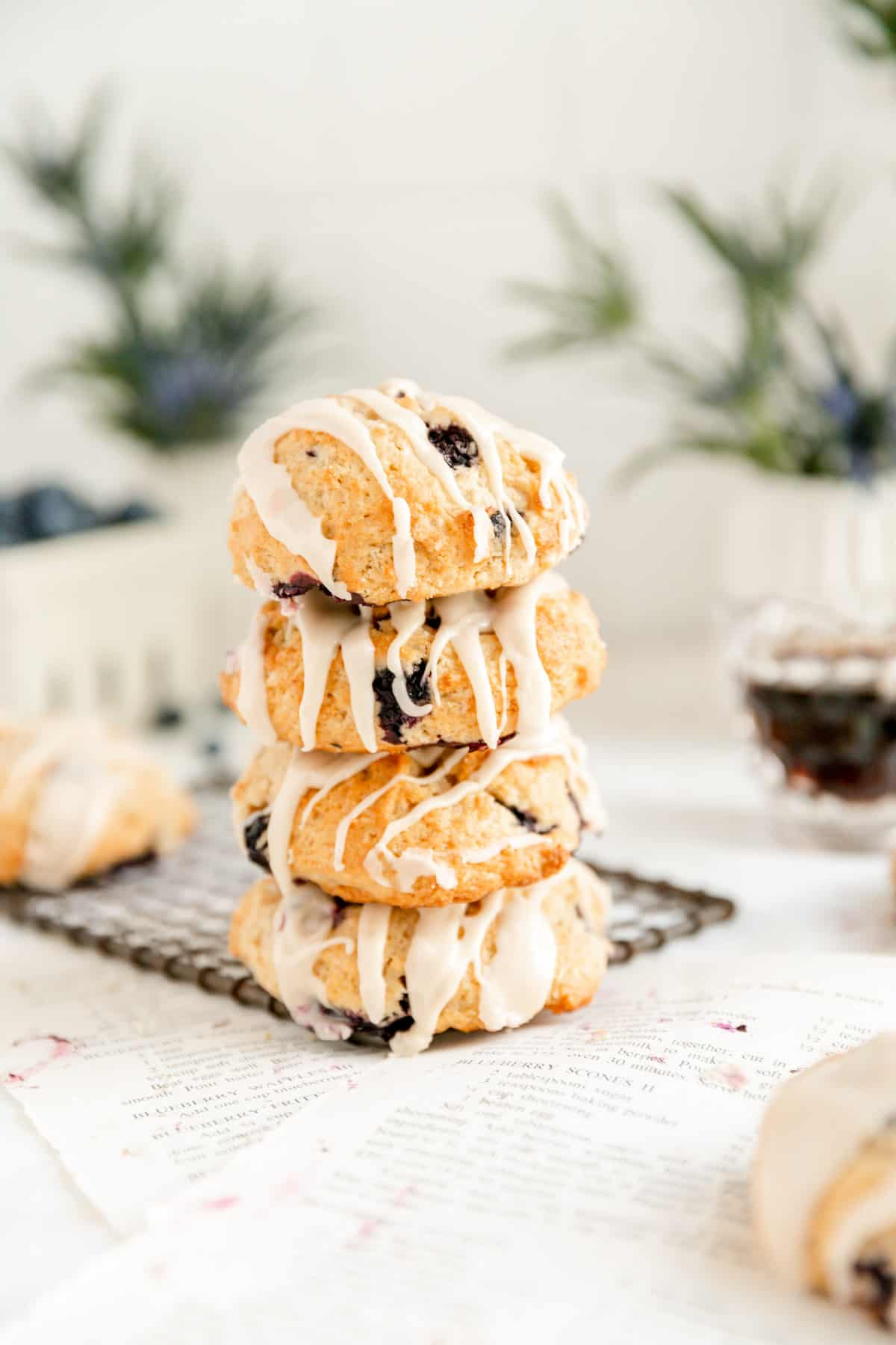 a stack of 4 blueberry scones on a dark wire rack with flowers and syrup pitcher