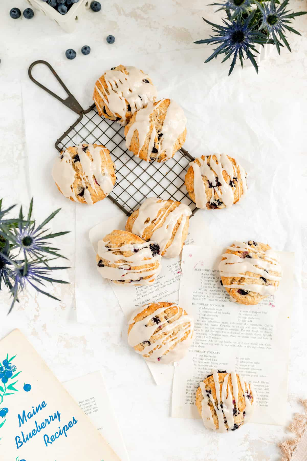 glazed scones on a wire rack and recipe pages from above with blue flowers and berries