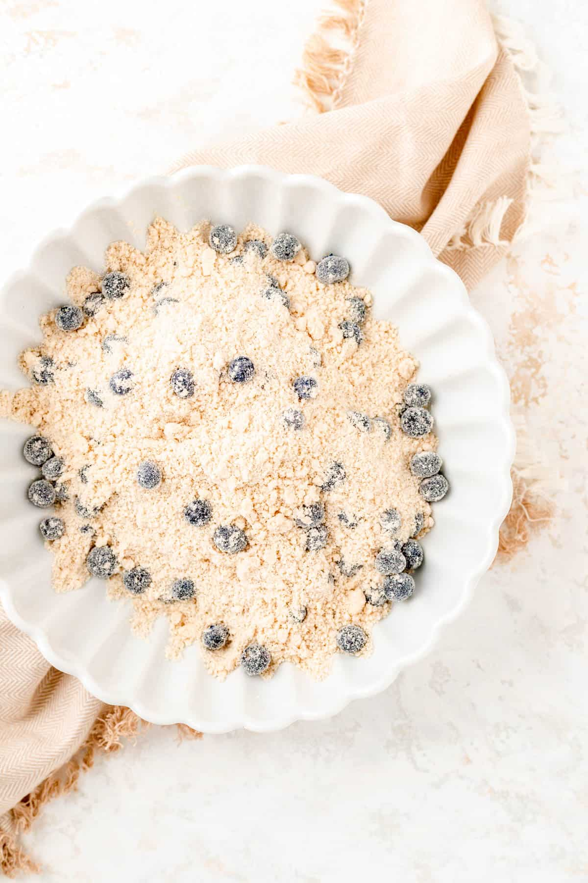 dry ingredients with butter cut in and blueberries as well in a white bowl