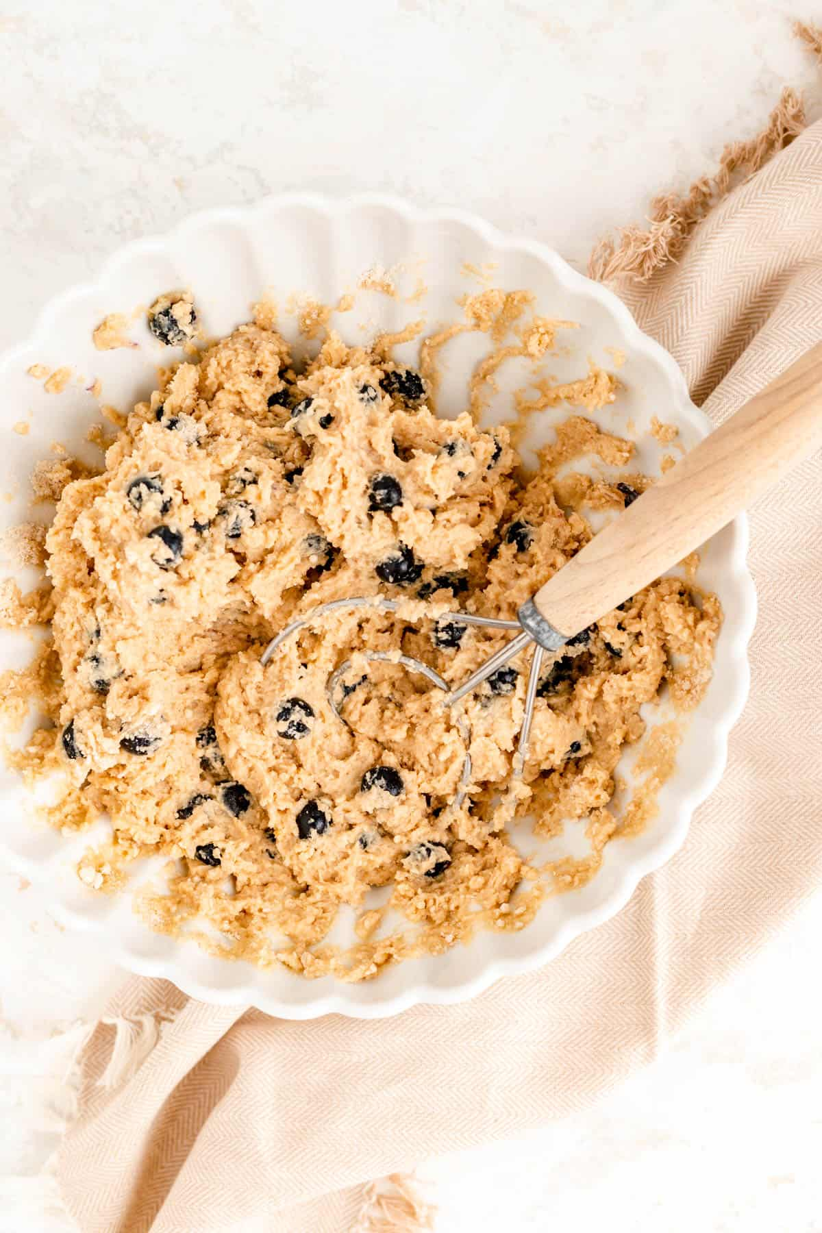 fully mixed blueberry scone batter in a white bowl with a dough whisk in it