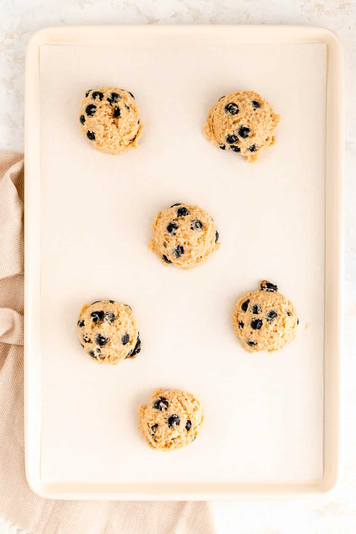scooped blueberry scone batter on a white parchment lined baking sheet