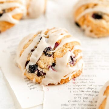close up of a glazed maple blueberry scone on torn out recipe pages
