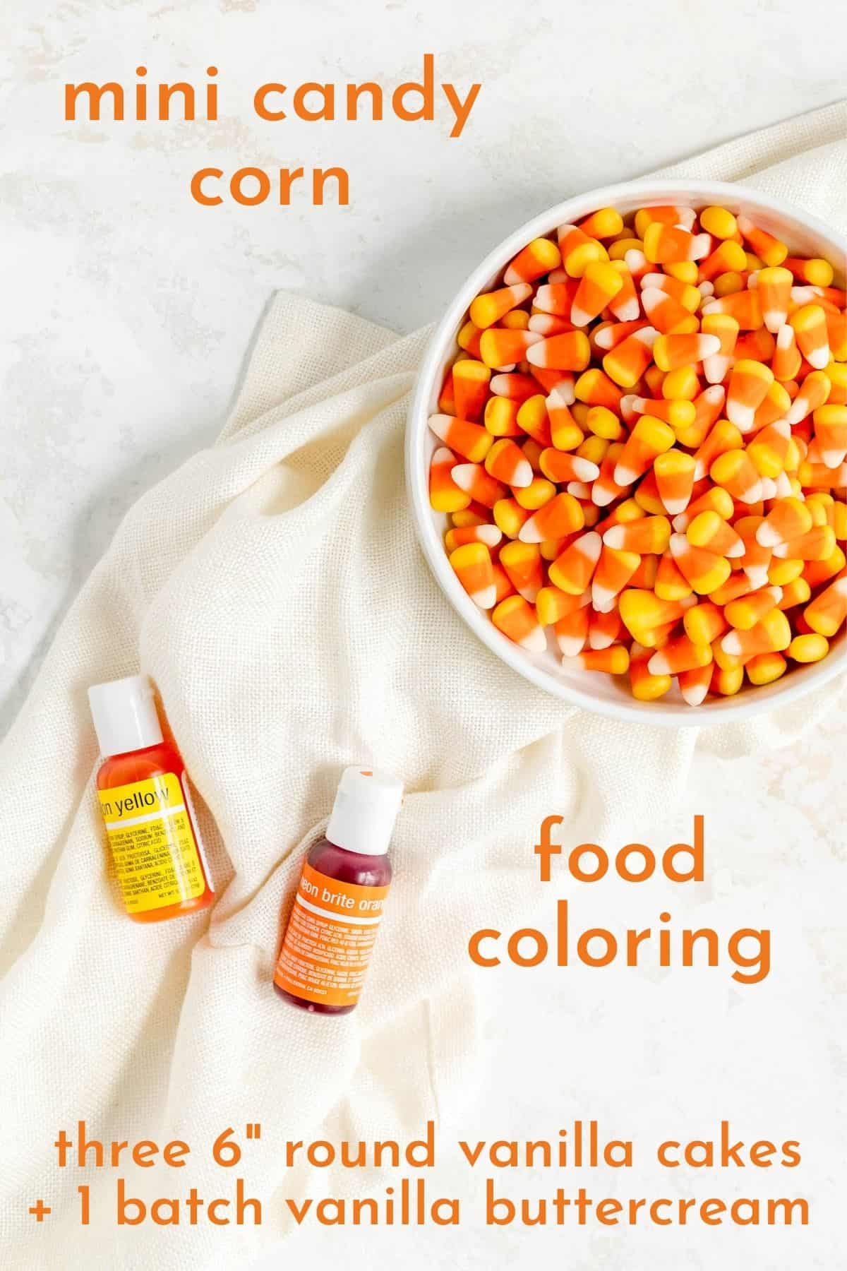 a bowl of mini candy corns and bottles of yellow and orange food coloring on white background