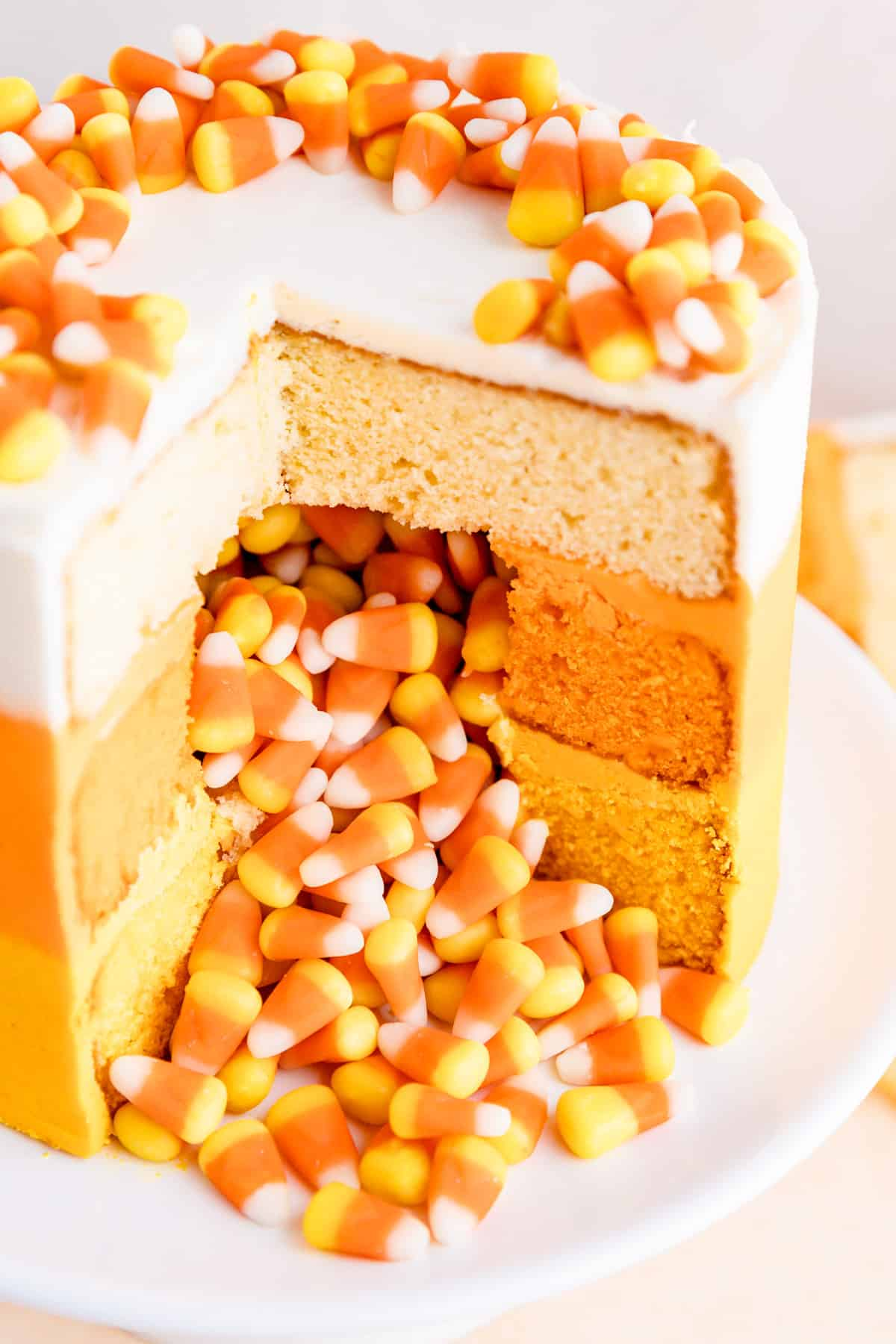 close up of slices candy corn decorated cake with candy corn spilling out of middle