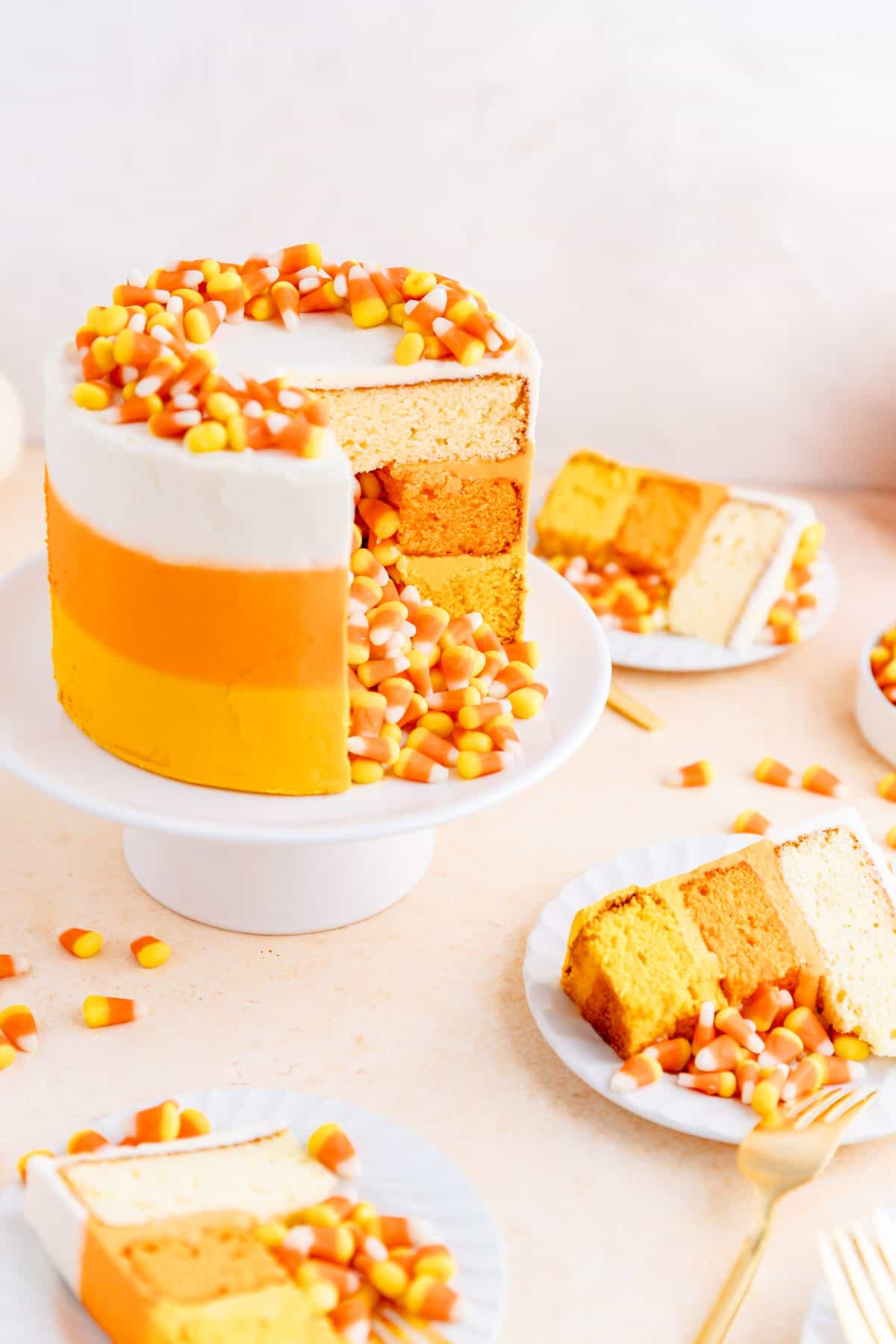 candy corn decorated cake with candy corn spilling out of middle with slices on plates