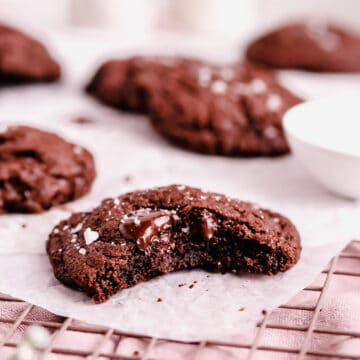 a dark chocolate chip cookies with sea salt with a bite out of it on a cooling rack